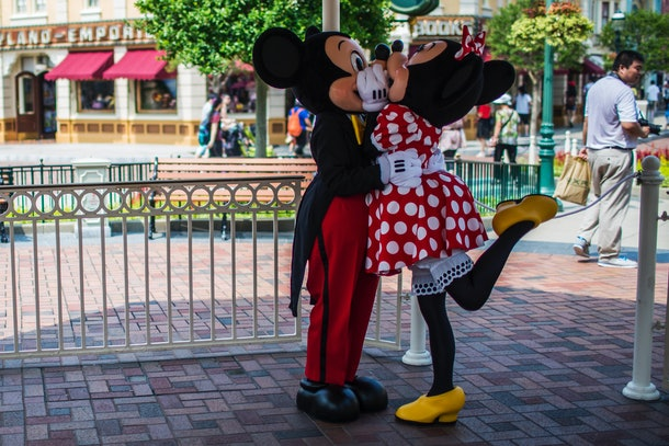 Mickey and Minnie Mouse share a kiss at Disneyland.