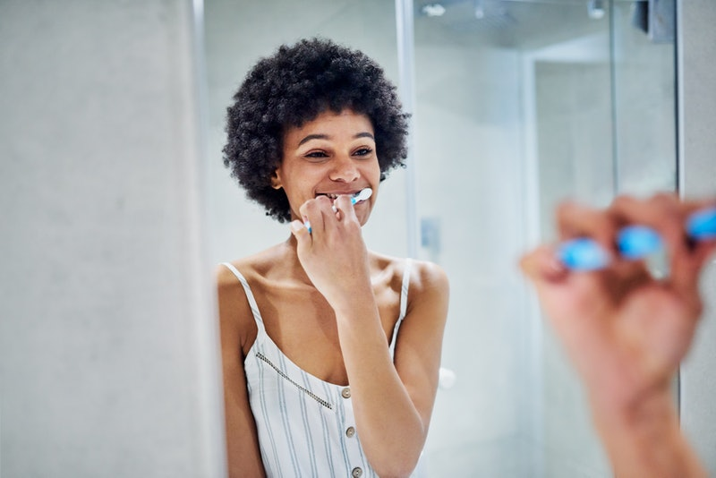 A person brushes their teeth in the mirror. Brushing teeth was linked to better heart health in a 2019 study.