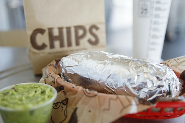 A Chipotle burrito sits in foil next to a side of guacamole and a bag of chips in the background. If you only order veggies on your burrito or burrito bowl, you can get guac for free.