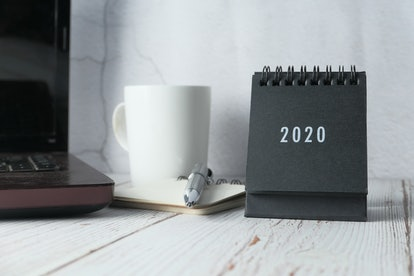 A black and white 2020 calendar sits next to a notebook and pen. Doodling about your success on a calendar can help you keep track of your progress toward your goals.