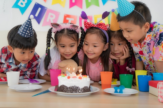 a group of kids at a birthday party with a cake