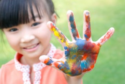 a little girl with paint all over the palm of her hand