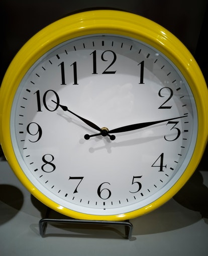 A yellow analogue clock sits on a stand. Give yourself less time to complete a task to help accomplish your goal more efficiently.