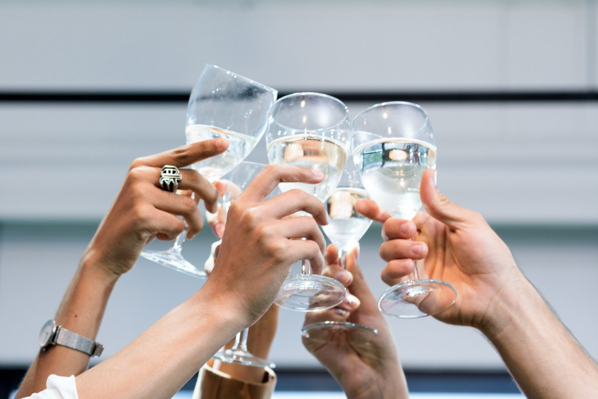 A group of friends holds up their glasses of champagne on New Year's Eve.