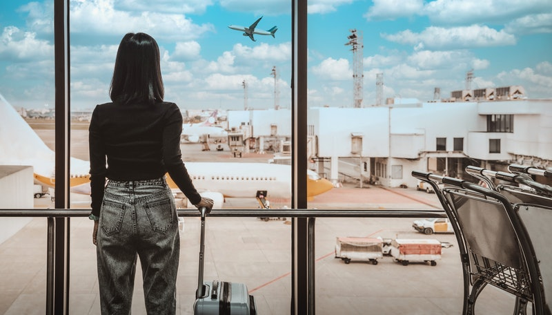A woman waits to board her plane. Boarding your plane before your zone is called is generally a no-no among travel experts.