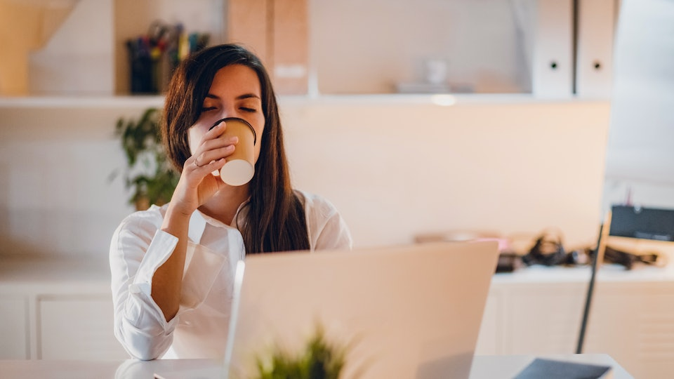 woman drinking coffee at desk at work