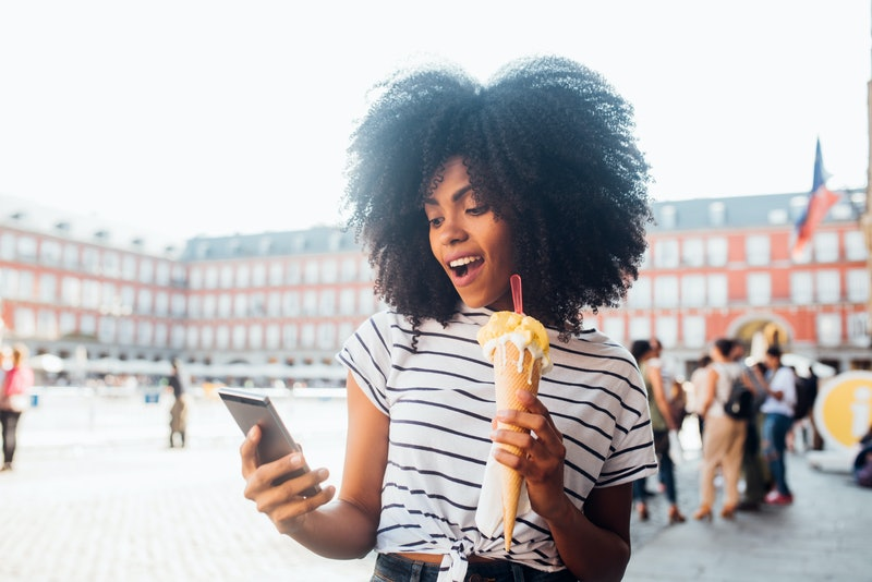 A woman traveling alone takes a selfie while eating an ice cream cone
