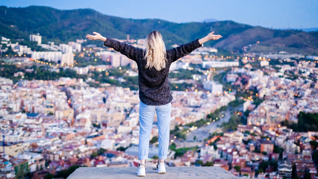 A blonde woman stands on a rock overlooking a city with her arms wide open.