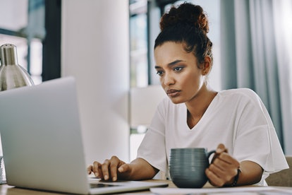 woman working on laptop and drinking coffee