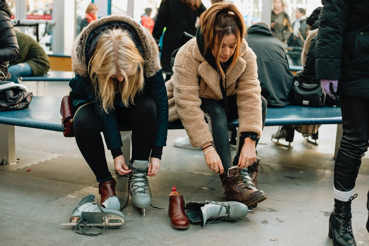 Two girls put on skates before ice skating on a rooftop in New York City.