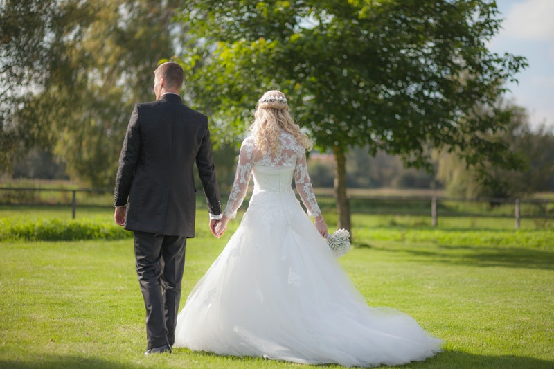 A bride and groom in a stock image walk through a field. Content that romanticizes plantation weddings will no longer be promoted on the knot or pinterest.