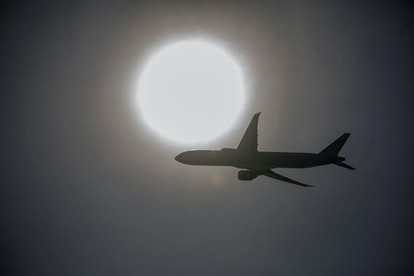 A plane flies across the sun. Air travel can cause a significant amount of damage to air quality and greenhouse gases, and carbon offset schemes aim to change that.