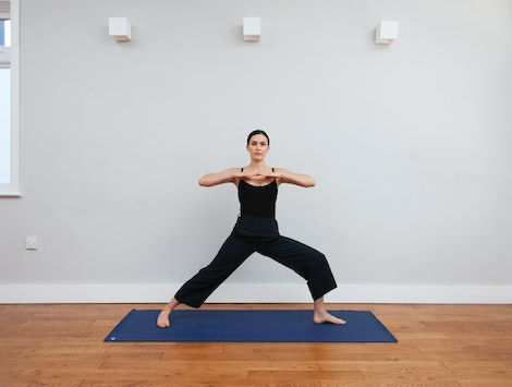 Adriene Mishler of Yoga with Adriene poses on a blue mat in a yoga studio. Gender-neutral language is important, even in fitness spaces, to be inclusive of trans and nonbinary people.
