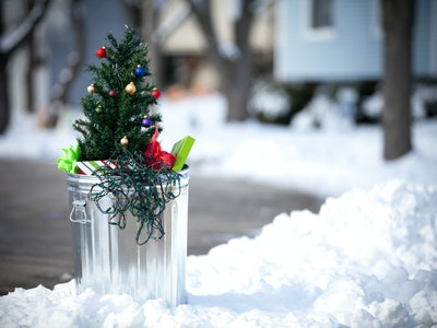 an artificial Christmas tree in the garbage
