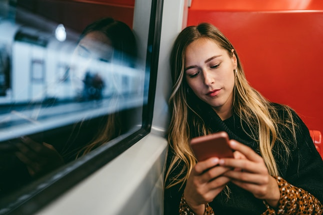 A person rides a train while looking at her smartphone. Instead of dopamine fasting, you should seek out a medical professional if you're concerned about smartphone addition, experts say.
