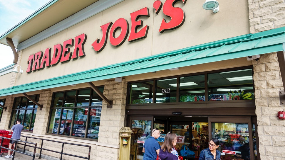 People enter and exit a Trader Joe's grocery store. Trader Joe's had recalled several pre-packaged food products due to possible Listeria contamination.