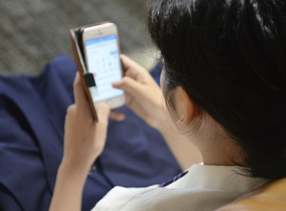 A person sits on a couch while looking at their smartphone. Dopamine fasting might just increase you...