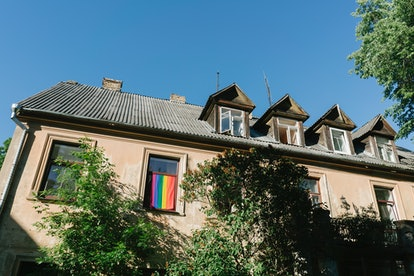 A rowhouse with a pride flag hanging from a window. LGBTQ housing discrimination is still legal, but lawmakers are trying to change that.