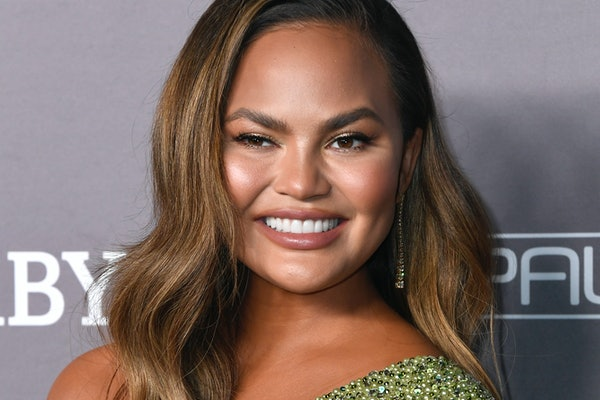 Chrissy Teigen hits the red carpet in a sage green dress.