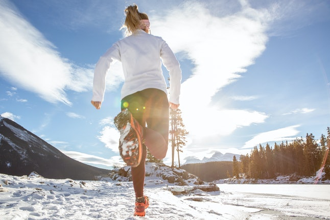 A woman runs in a snowy landscape. As days become longer and hotter after the winter solstice, our circadian rhythms may shift slightly, experts say.
