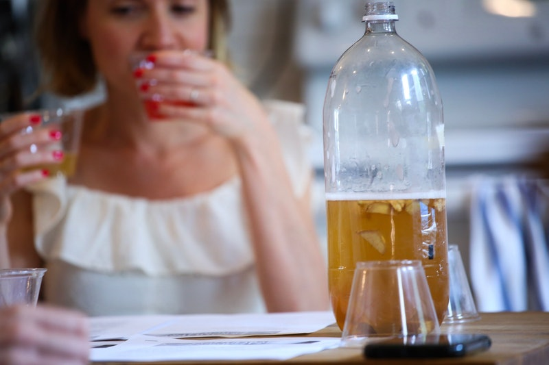 A woman drinks kombucha. Kombucha can be a delicious alternative to alcohol.