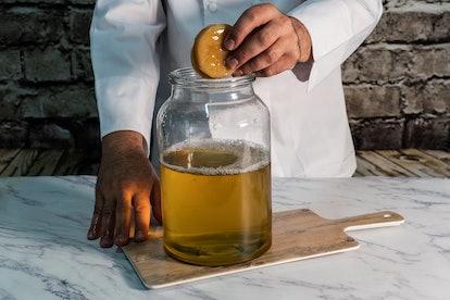 A kombucha-maker with their bottle of kombucha. Kombucha doesn't automatically improve gut health, despite claims.
