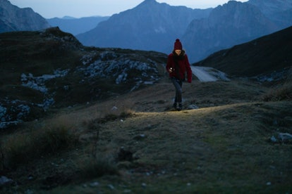 A woman walks in a dark winter landscape. Darker mornings in winter may contribute to SAD, or seasonal affective disorder.