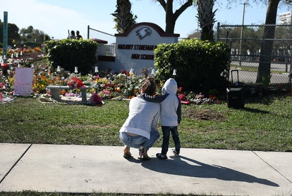 PARKLAND, FLORIDA - FEBRUARY 14:  Jaxon Creed (R) hugs Destiny Calero who graduated in 2013 as they visit a memorial setup at Marjory Stoneman Douglas High School in honor of those killed during a mass shooting on February 14, 2019 in Parkland,  Florida. A year ago on Feb. 14th at Marjory Stoneman Douglas High School 14 students and three staff members  were killed during the mass shooting. (Photo by Joe Raedle/Getty Images)