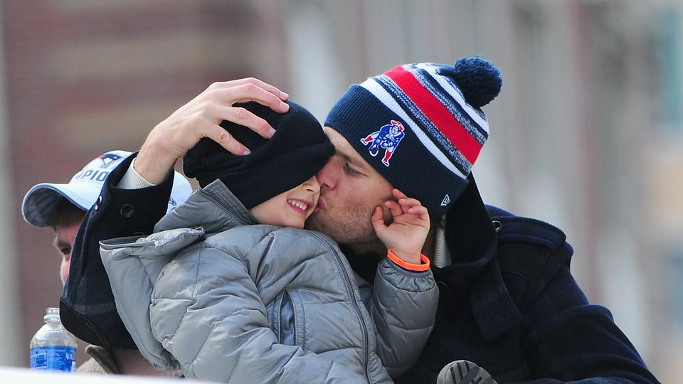 BOSTON, MA - FEBRUARY 04:  Quarterback Tom Brady of the New England Patriots kisses his son Benjamin during a Super Bowl victory parade on February 4, 2015 in Boston, Massachusetts. The Patriots defeated the Seattle Seahawks 28-24 in Super Bowl XLIX. (Photo by Billie Weiss/Getty Images)