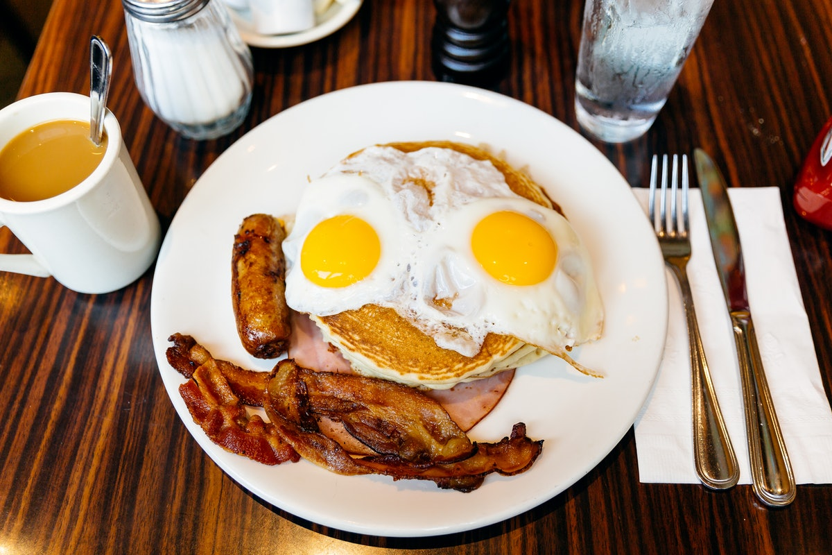 A breakfast at a local diner features eggs, bacon, pancakes, and coffee.