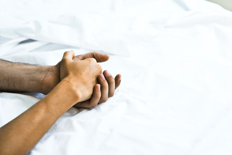 A couple holds hands in bed after sex. Orgasms are different for everyone, but here's what science s...