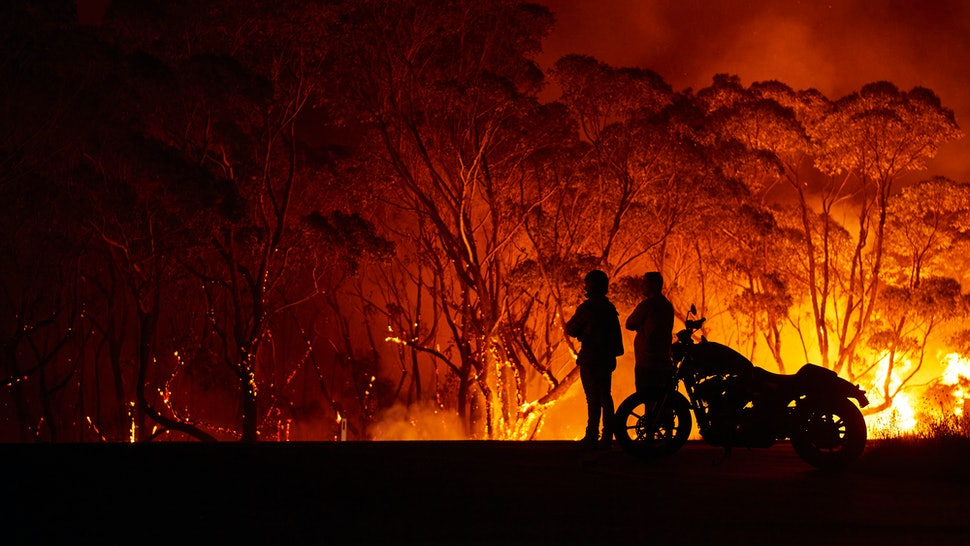 Onlookers watch Australian bushfires. The fires of the 2019-20 fire season have been the most destructive in history, in large part because of climate change, experts say.