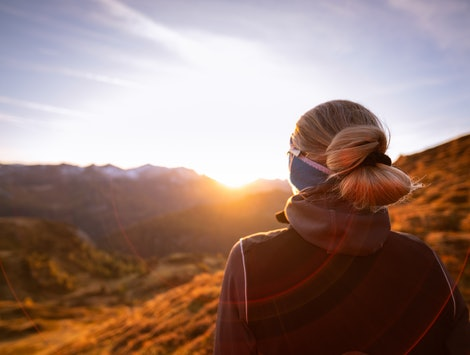 A woman looks at the sunset. Early menopause can occur in as many as one percent of all women, according to experts.
