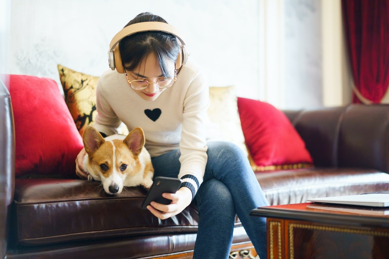 A person hugs her dog while listening to music. Listening to music with your pet is about to get much easier, as Spotify launches its Pet Playlists to help customize music for your pet.