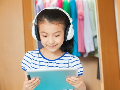 a little girl with headphones listening to audiobook and reading along