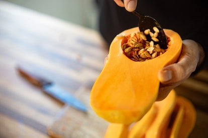 A close up image of a person's hands, holding half of a winter squash while using a spoon to scoop out the seeds. Winter squash is one of many foods that is rich in vitamins you need to fight the flu.