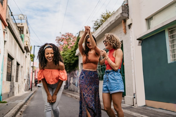 Three friends laugh and dance in the street of a colorful city while on vacation.