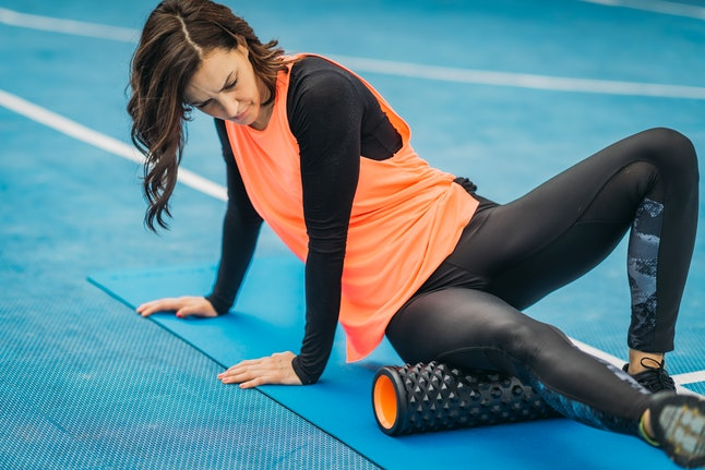 A person wearing an orange tank top over a black long-sleeved shirt concentrates while she foam rolls her lower body. Foam rolling can help you prepare to sprint, but you might not want to foam roll before a long run.