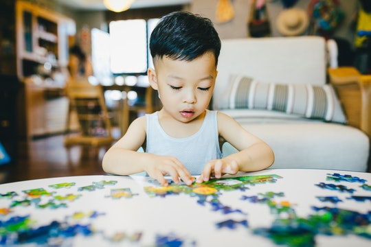 a little boy putting a puzzle together