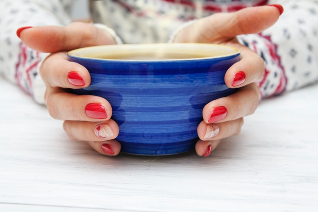 A woman holds a cup of coffee. Intermittent fasting can damage your relationship with food and hunger cues, experts say.