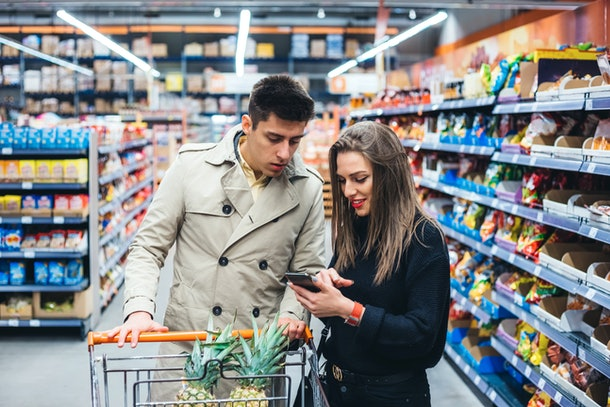 A young couple looks at a phone while going grocery shopping together.