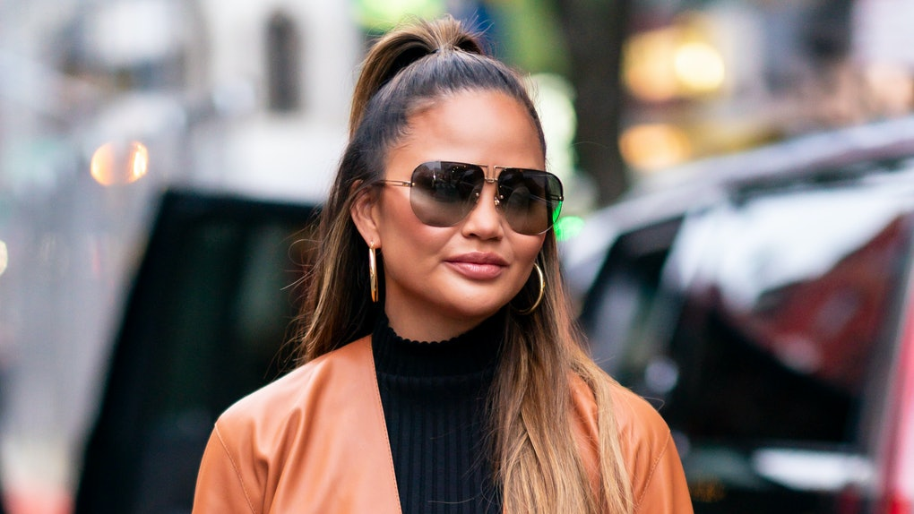 Chrissy Teigen hits the streets in a brown leather jacket.