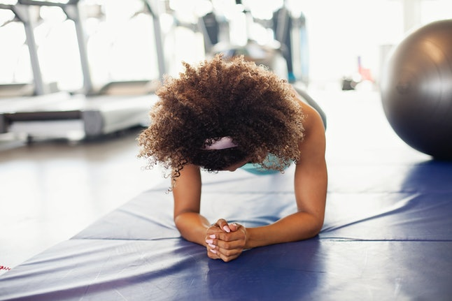 A woman holds a plank. Starting to exercise in the morning is a helpful habit for lifelong fitness.