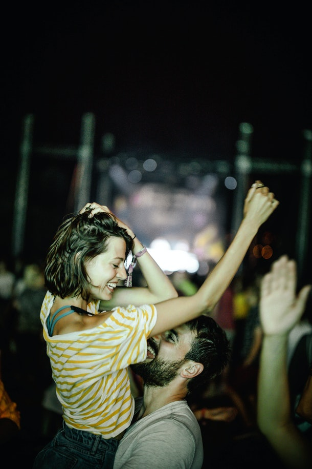 A woman dances with her SO at a lively concert while on a trip.