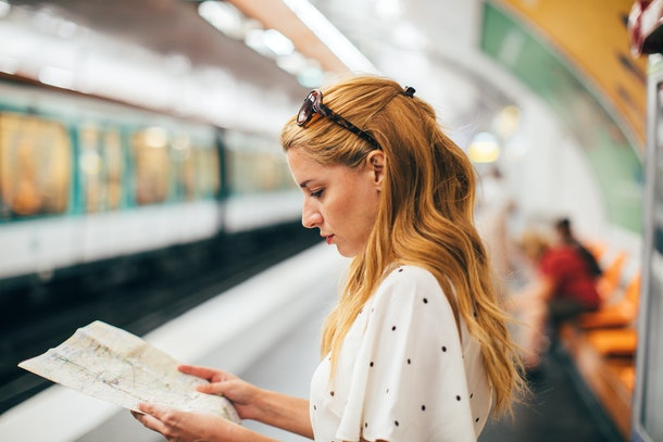 A red-haired woman looks at a map in a subway station while on vacation.