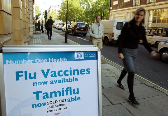 a sign for flu vaccines and Tamiflu on a city sidewalk