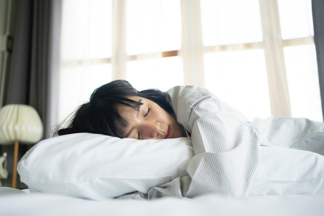 A woman sleeps. Adjusting your bedtime to fit your chronotype might help your sleep patterns.
