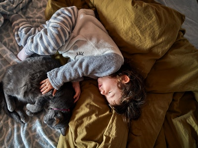 a toddler and cat napping together on a bed
