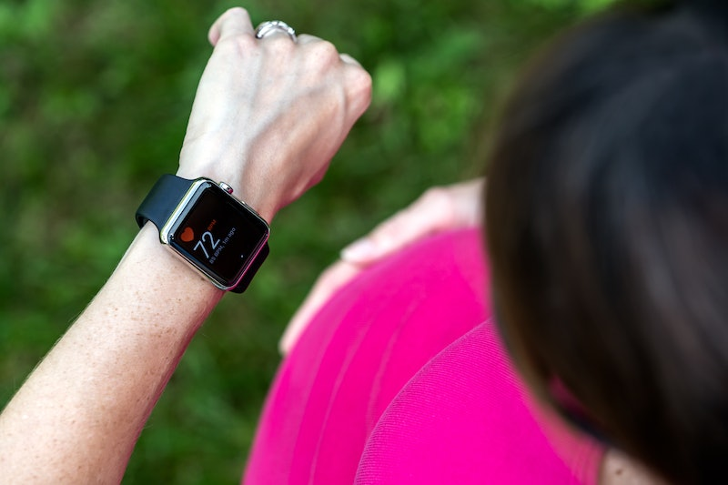 A user wearing a pink shirt checks her Apple Watch. Apple Watch Connected is a new fitness incentives program that might be coming to a gym near you.