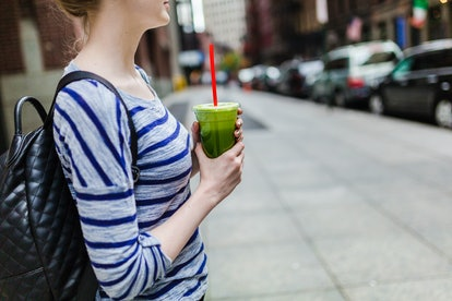 A woman holds a green smoothie. Not drinking alcohol has the unexpected benefit of making you want to drink less.
